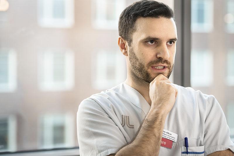 Jim Alkas, specialist i internmedicin och ST-läkare i njurmedicin, är orolig för att arbetsbördan blir orimlig när Karolinska universitetssjukhuset ska dra ner på antalet läkare. Foto: Anders G Warne