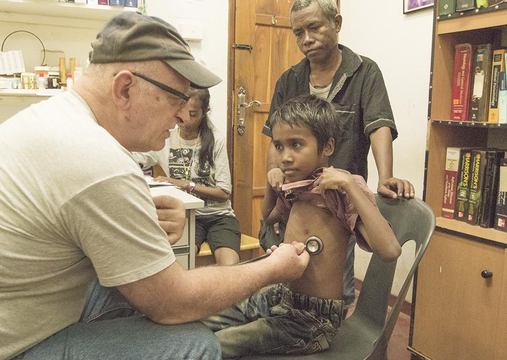 Doktor Dan Murphy undersöker en pojke som kom med sin far till gratiskliniken för att få sjukvård. Administrationen sköts av klinikens läkarsekreterare (sittande i bakgrunden). Foto:Pouya Ghelichkhan