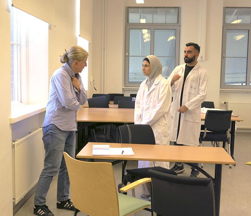 En patient, gestaltad av Annika Nordin, ber två av 2018 års kompletteringsstudenter, Fatima Al-Yakoubi och Sarmad Dhahir Hameed, om hjälp. Foto: Henrik Sjövall