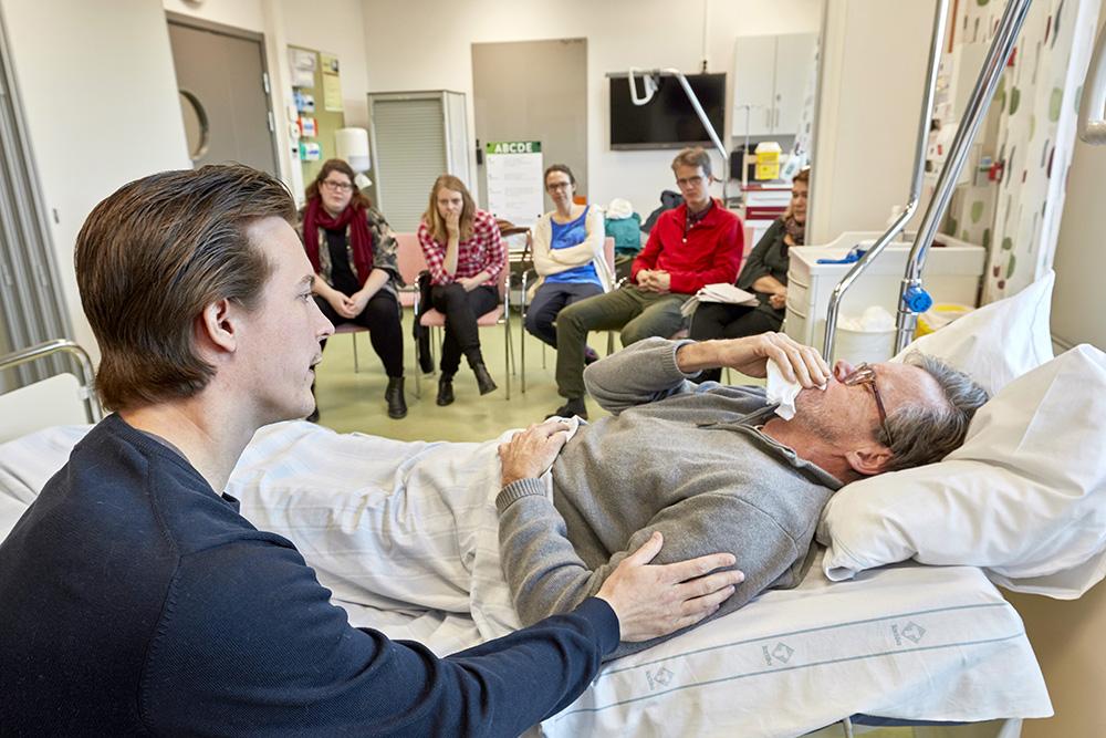 »Allt som inte är en ledsen patient – som en arg eller tyst till exempel – tycker jag är svårt. Ledsen är liksom normalen, det andra är jag inte så van vid att möta«, säger Niklas Holmlöv, ST-läkare i kirurgi, som här tränar på 'patienten' Rolf. Foto: Mats Samuelsson